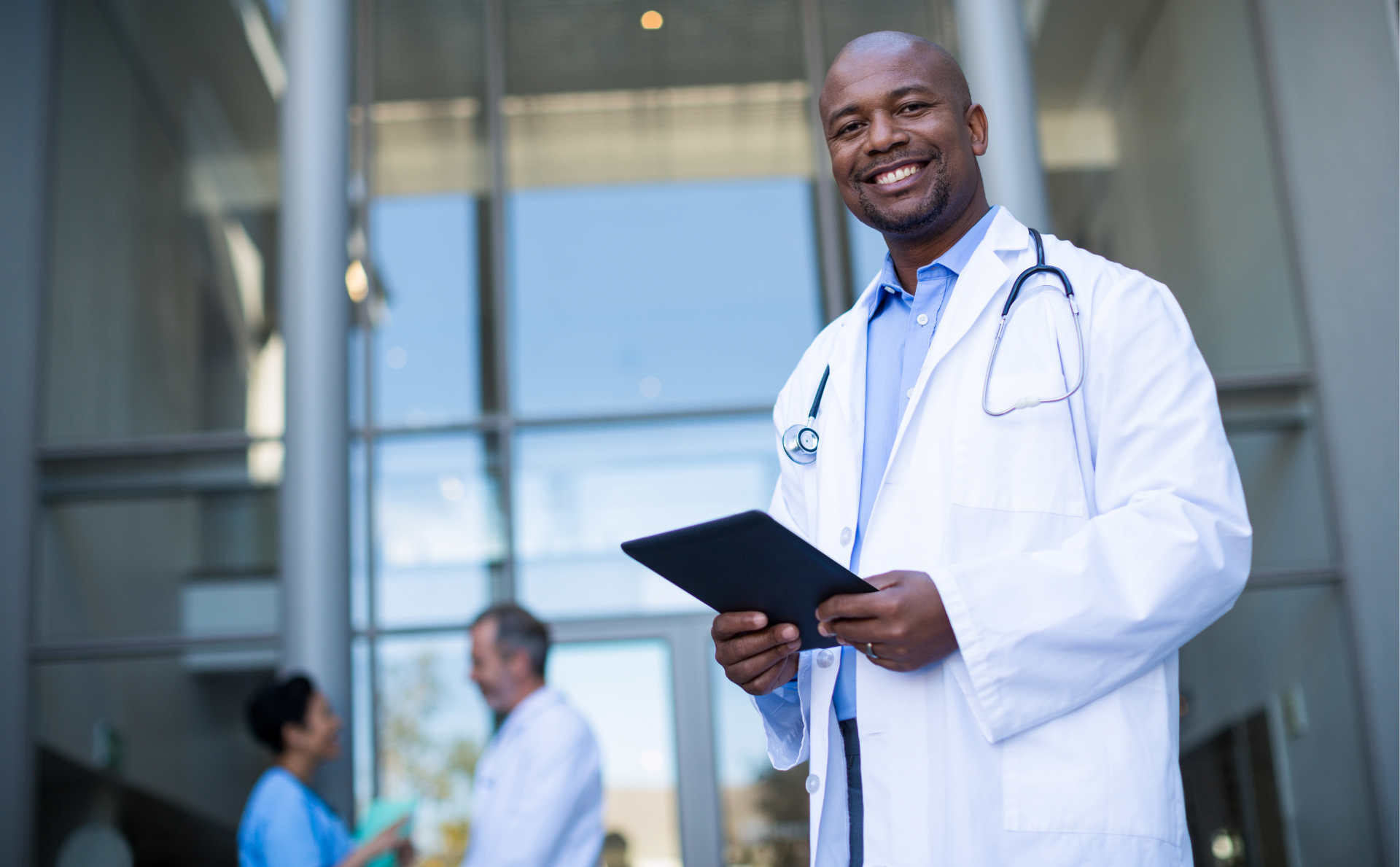 Doctor standing in a lab coat in front of a hospital smiling and holding a clip board